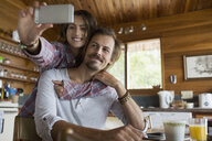Affectionate young couple taking selfie in cabin kitchen - HEROF27840