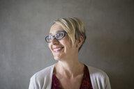 Portrait smiling blonde businesswoman with eyeglasses looking away - HEROF27886