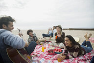 Friends hanging out playing guitar picnicking on beach - HEROF27916