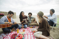 Friends hanging out playing guitar picnicking on beach - HEROF27919