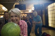 Enthusiastic woman with friends bowling at bowling alley - HEROF27952
