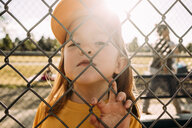 Close-up portrait of cute girl wearing cap standing against sky seen through chainlink fence during sunny day - CAVF62890