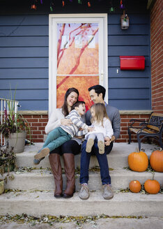 Happy family sitting on steps against house during Halloween - CAVF62893