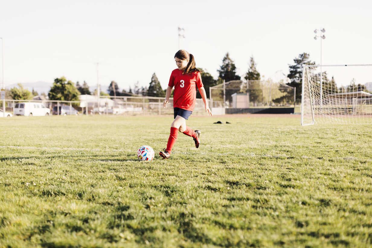 Full length of girl wearing uniform kicking soccer ball on field - CAVF62929 - Cavan Images/Westend61