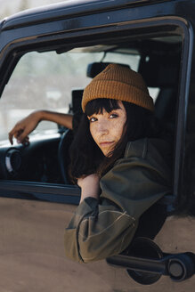 Portrait of woman wearing warm clothing sitting in off-road vehicle - CAVF62957