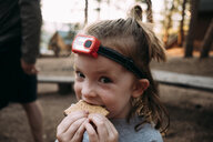 Close-up portrait of cute girl eating sweet food while standing in forest - CAVF62963