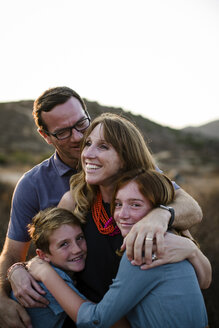 Portrait of happy siblings with parents standing on field during sunset - CAVF62969