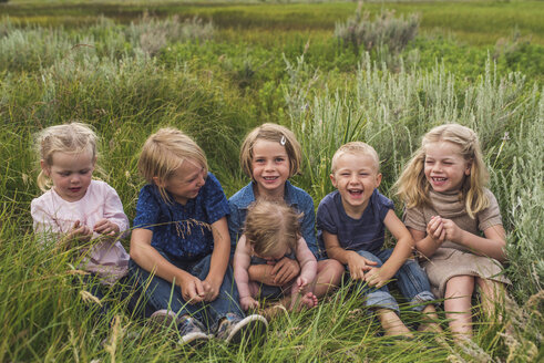 Cute happy friends sitting together on field by plants - CAVF62984