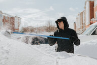 Man clearing snow-covered vehicle with broom, Toronto, Canada - ISF20961