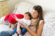 Mother reading to baby girl on sofa - ISF20982