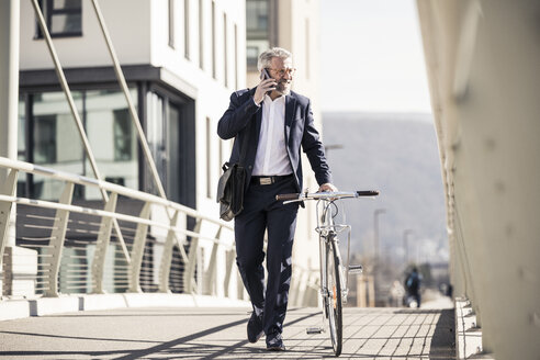 Smiling mature businessman with bicycle talking on cell phone in the city - UUF16620