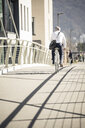 Rear view of mature businessman riding bicycle on a bridge in the city - UUF16632