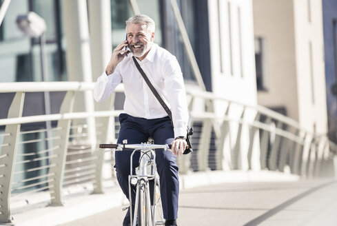Happy mature businessman talking on cell phone and riding bicycle on a bridge in the city - UUF16635