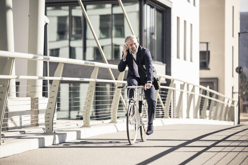 Smiling mature businessman with headphones riding bicycle on a bridge in the city - UUF16641