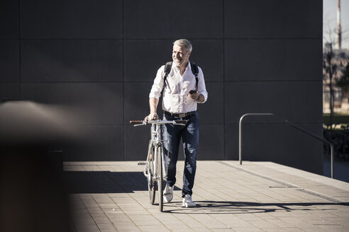 Smiling mature businessman with bicycle, cell phone and earphones on the go - UUF16644
