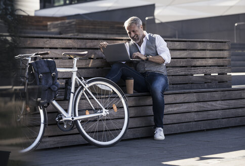 Smiling mature businessman with bicycle sitting on a bench using laptop - UUF16647