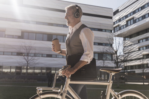 Smiling mature businessman with bicycle, takeaway coffee and headphones on the go in the city - UUF16653