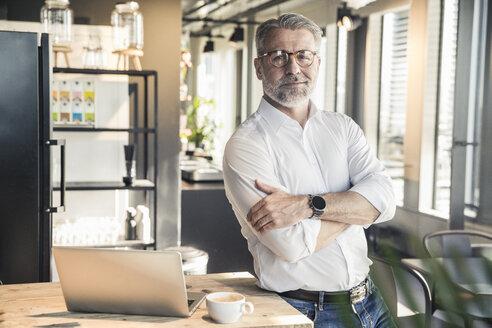 Portrait of confident mature businessman in office - UUF16680