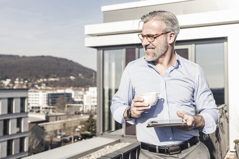 Smiling mature businessman with cup of coffee and tablet on roof terrace - UUF16689
