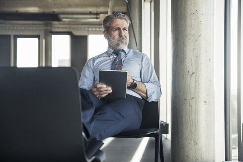 Mature businessman sitting on chair using tablet - UUF16698