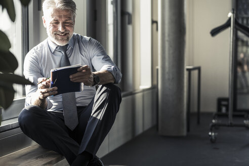 Smiling mature businessman sitting at the window with notebook - UUF16701