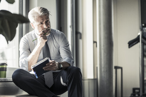 Mature businessman sitting at the window with notebook - UUF16704