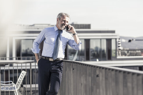 Smiling mature businessman on cell phone on roof terrace - UUF16713