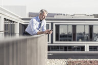 Mature businessman using cell phone on roof terrace - UUF16716