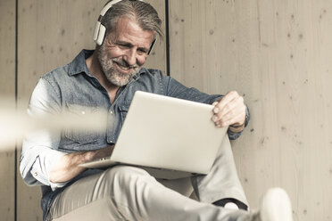 Casual mature businessman sitting down with laptop and headphones - UUF16725