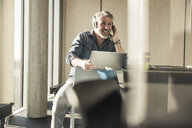 Casual mature businessman sitting down with laptop and headphones - UUF16728