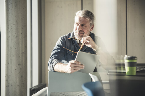 Casual mature businessman sitting at desk with tablet - UUF16731