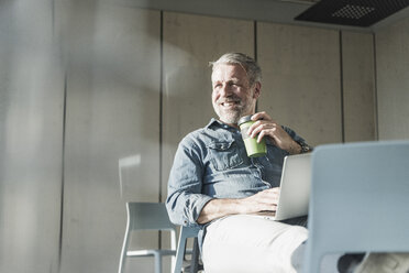 Smiling casual mature businessman with laptop and takeaway coffee - UUF16734
