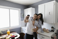 Happy young Latinx couple taking selfie in morning kitchen - HEROF27967