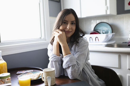 Portrait confident young Latinx woman eating breakfast in kitchen - HEROF27970