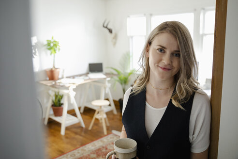 Portrait confident woman drinking coffee in home office doorway - HEROF28000