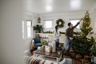 Young couple decorating Christmas tree in living room - HEROF28009