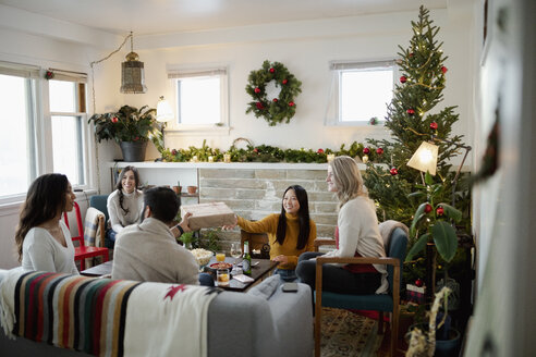 Friends opening Christmas gifts in living room - HEROF28018