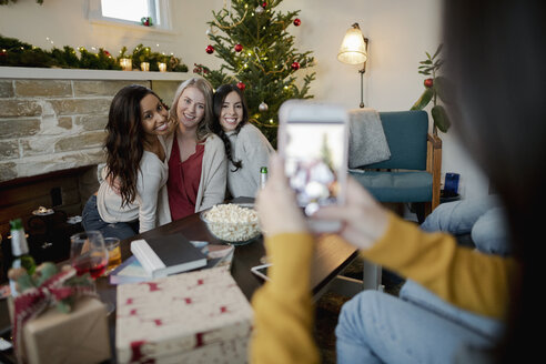 Woman with smart phone photographing friends in Christmas living room - HEROF28027