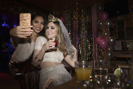 Bachelorette and friend taking selfie and drinking cocktails in nightclub - HEROF28042