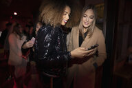 Women friends using smart phone in nightclub queue - HEROF28072