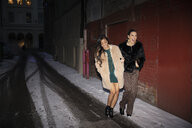 Women friends leaving nightclub, walking on snowy urban street - HEROF28090