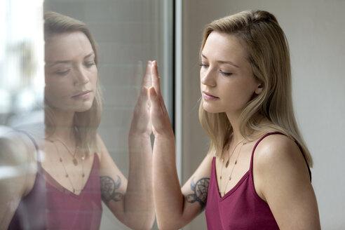 Deutschland,NRW,Ruhrgebiet,Stadt Essen,junge Frau spiegelt sich im Fenster - FLLF00061