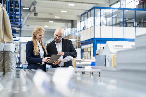 Businessman and businesswoman with tablet discussing in factory - DIGF06053