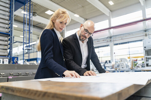Businessman and businesswoman looking at plan on table in factory - DIGF06089