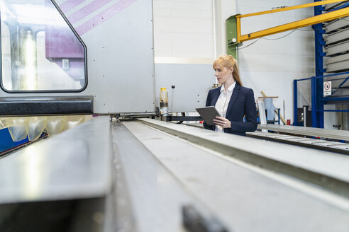 Businesswoman with tablet at conveyor belt in factory - DIGF06095