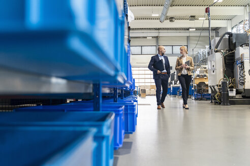 Businessman and businesswoman walking and talking in factory - DIGF06098