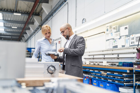 Businessman and businesswoman examining workpiece in factory - DIGF06122