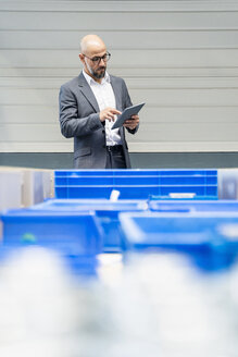 Businessman with tablet checking stock in factory - DIGF06128