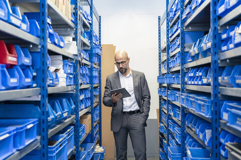 Businessman with tablet in factory storehouse - DIGF06131