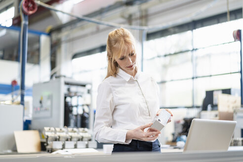 Businesswoman with laptop examining workpiece in factory - DIGF06149